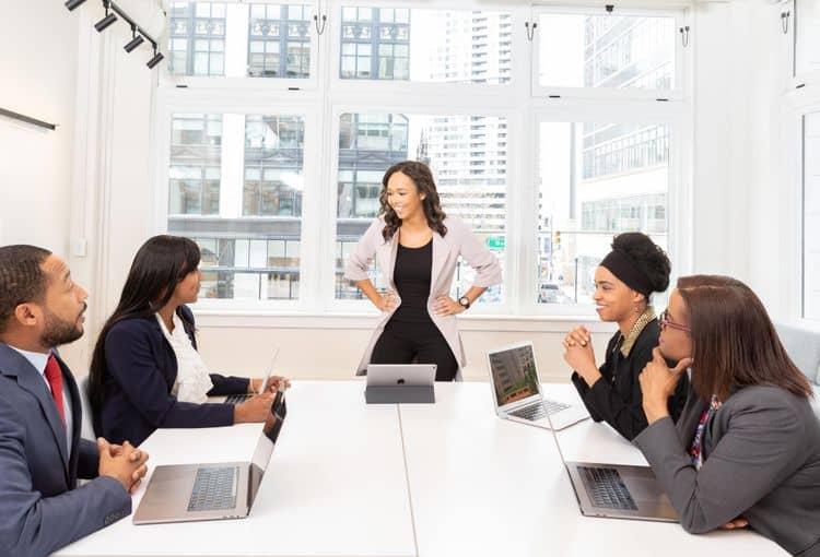 Gruppe von Mitarbeitern, die an Tisch sitzen