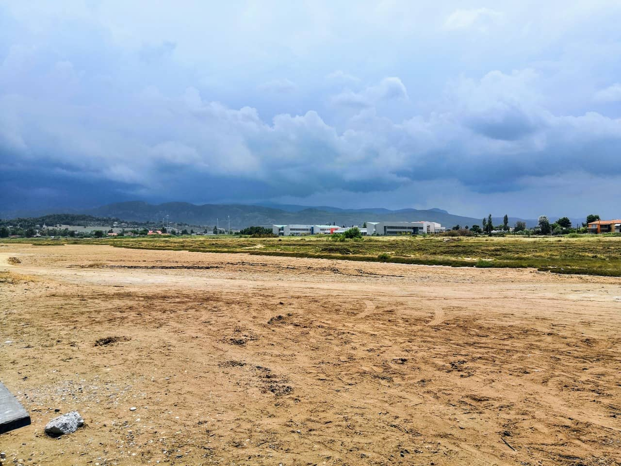Cloudy view of buildings from a dirt road