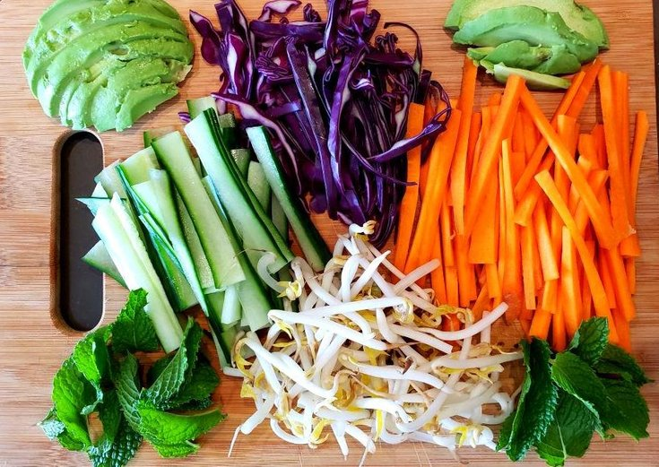 Cutting board with carrots, red cabbage, avocado, sprouts, mint, cucumber