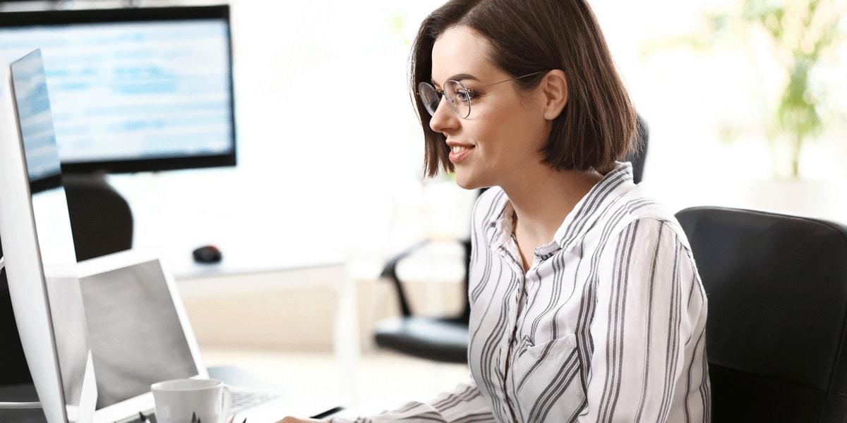 An aspiring web developer sitting at a desk, looking at a computer screen