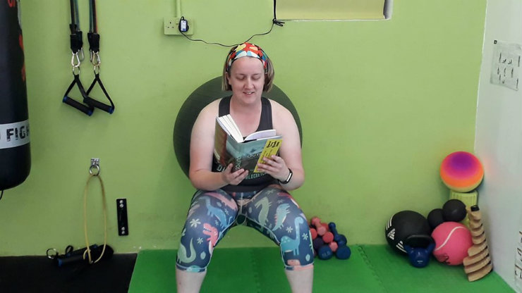 Newmarket Library manager Kate Ashton enjoys a book while working out at the gym
