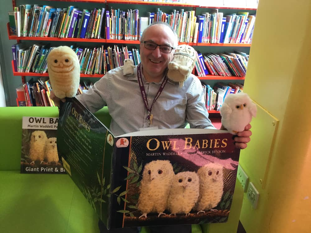 A man reading a huge hardback book with owl toys around him.