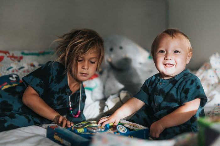 hermanos jugando cama