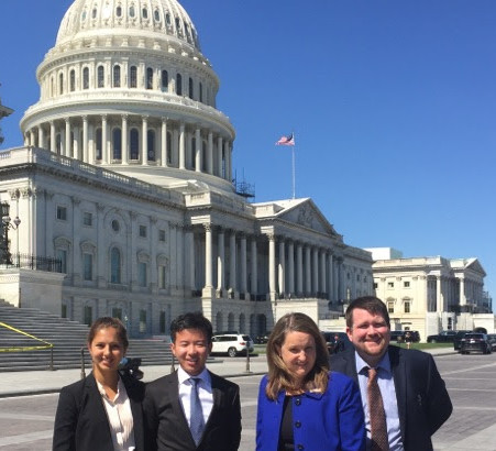 four advocates standing before the US Capitol, renovations nearly complete.