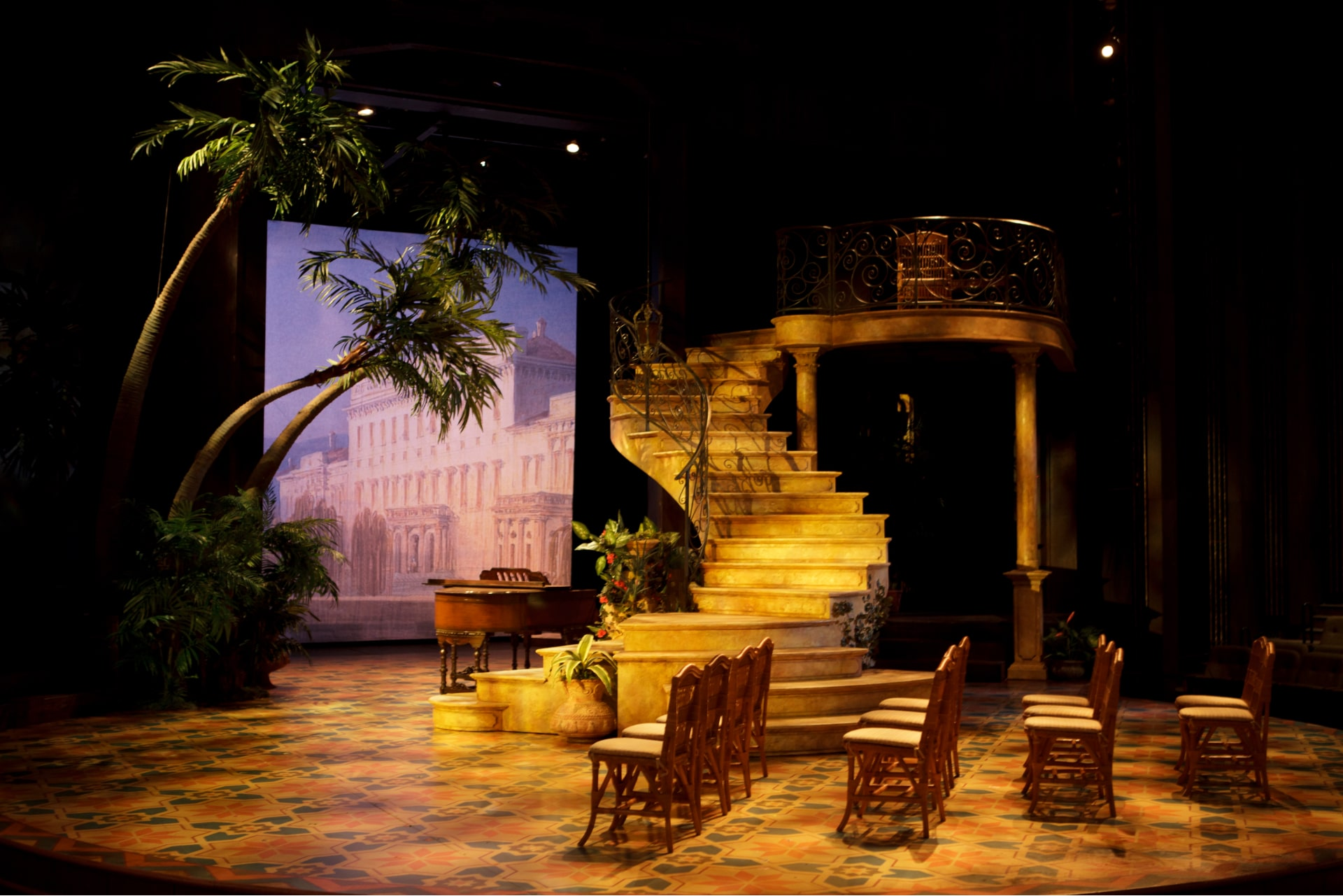 Curved staircase on tiled empty stage with chairs, piano and palm trees.
