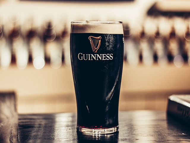A pint of Guinness in a Guiness pint glass