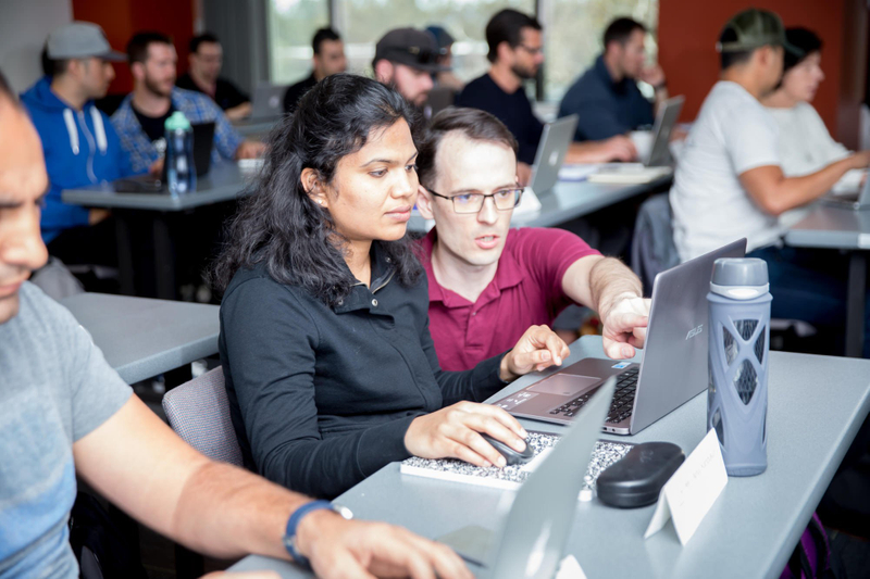 Instructor kneeling down to help student at computer