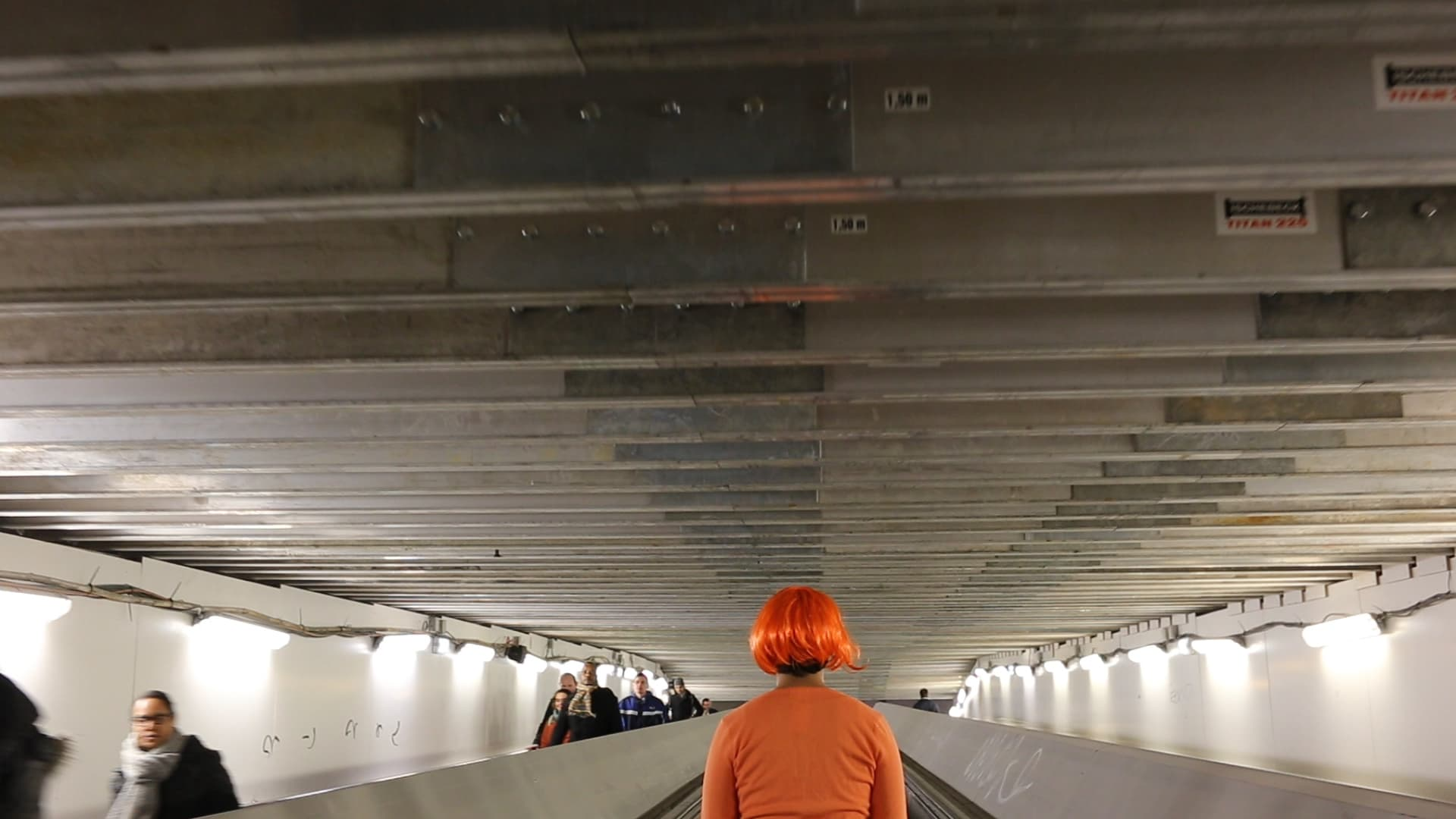Still from the film Network/Intersect, by Ollie Palmer. The image depicts a person wearing an orange wig on an escalator.