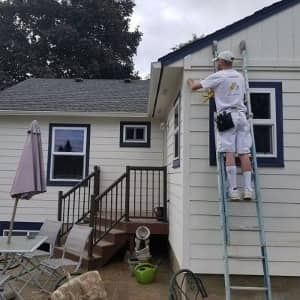 man on ladder painting a white home
