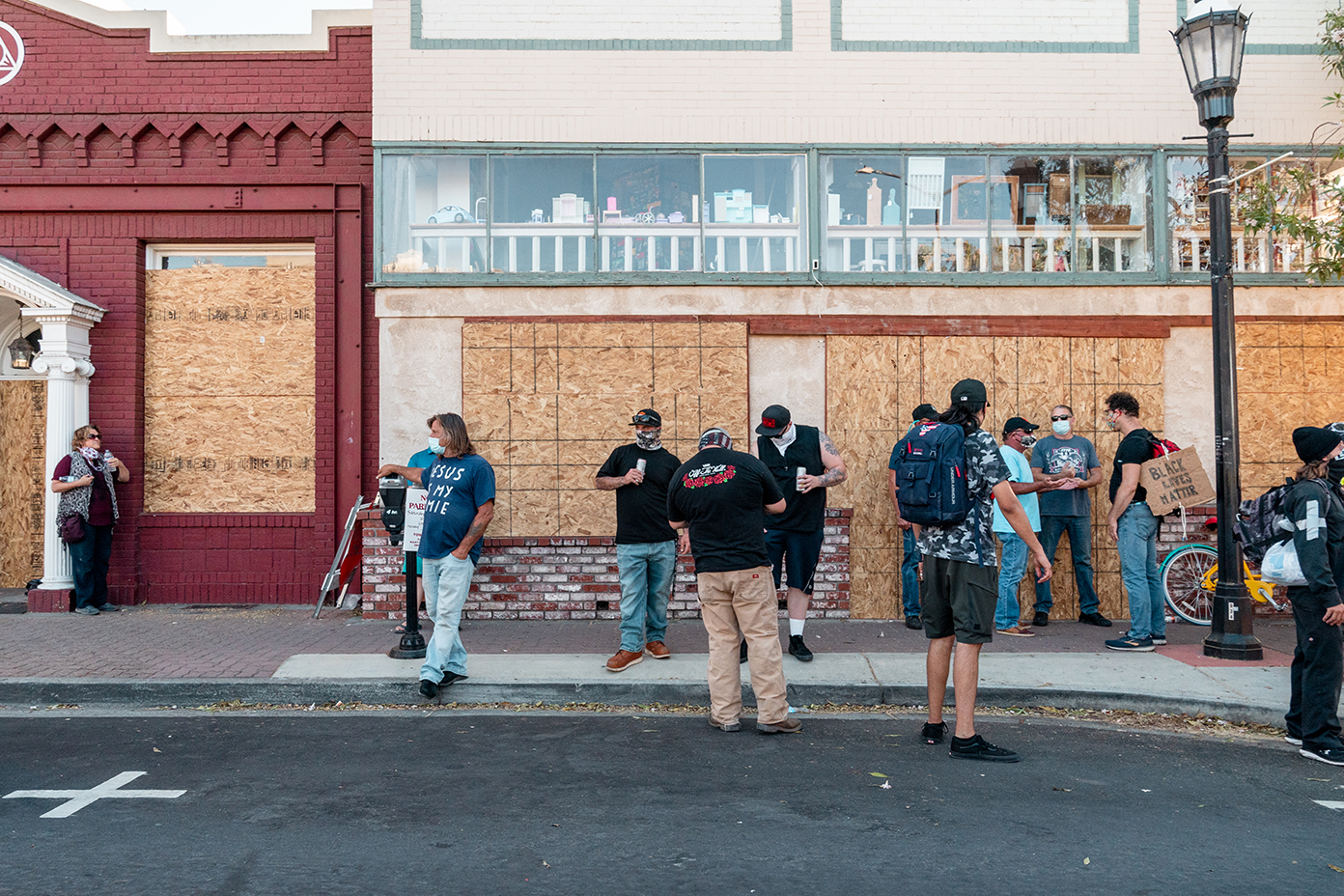 "A group including some counter protesters have conversations while drinking in public during the ""Zero Tolerance for White Supremacy"" protest in Martinez, Calif., on Sunday, July 12, 2020."