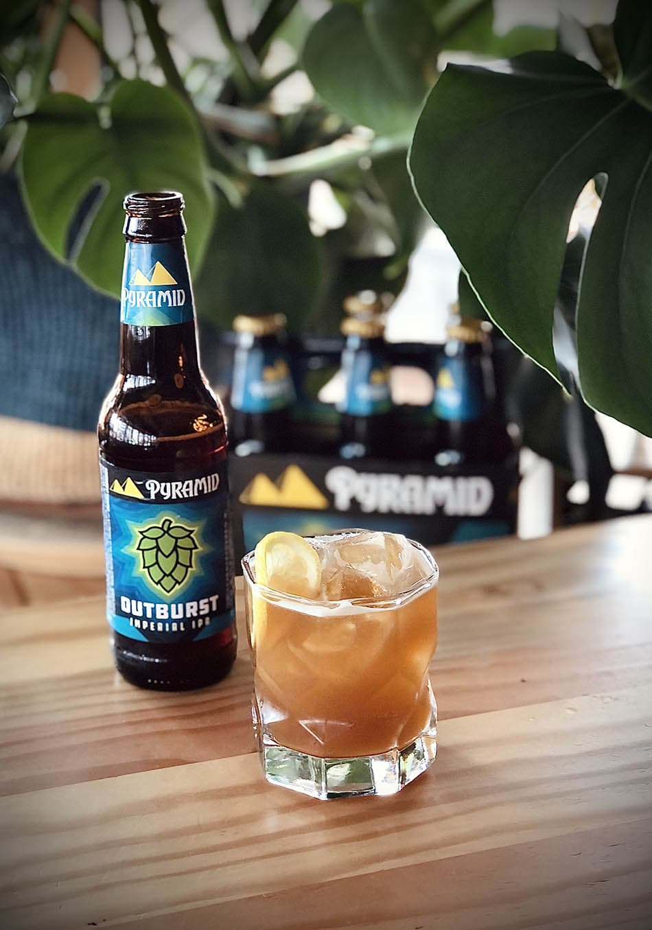 A tumbler full to the brim of the Outburst IPA beer cocktail called the Pacific Summer. The beer, peach brandy, and tea cocktail is positioned next to a bottle of Outburst IPA, a 6 pack, and some greenery.