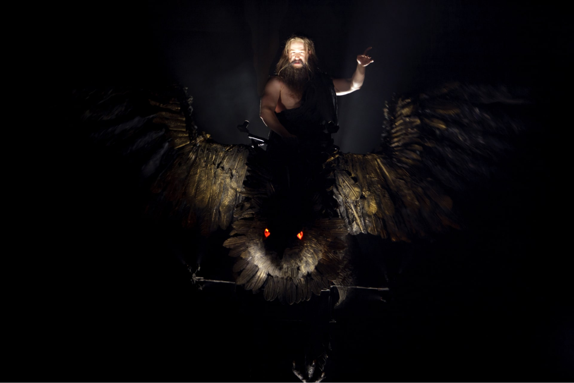 Bearded god rides giant, red-eyed bird in strong shaft of light.