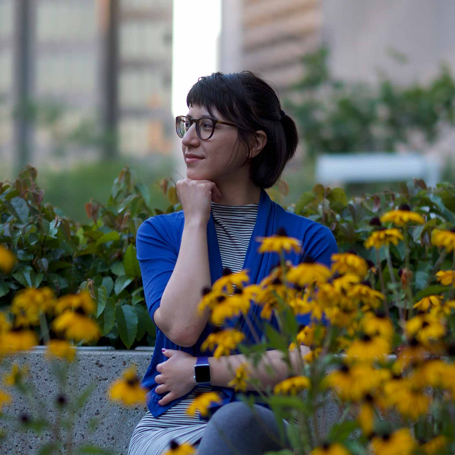 Gwen is sitting amongst flowers, her hand to her chin. She has dark hair that lays gently over her dark framed glasses. Gwen is wearing a blue cardigan over a striped shirt.