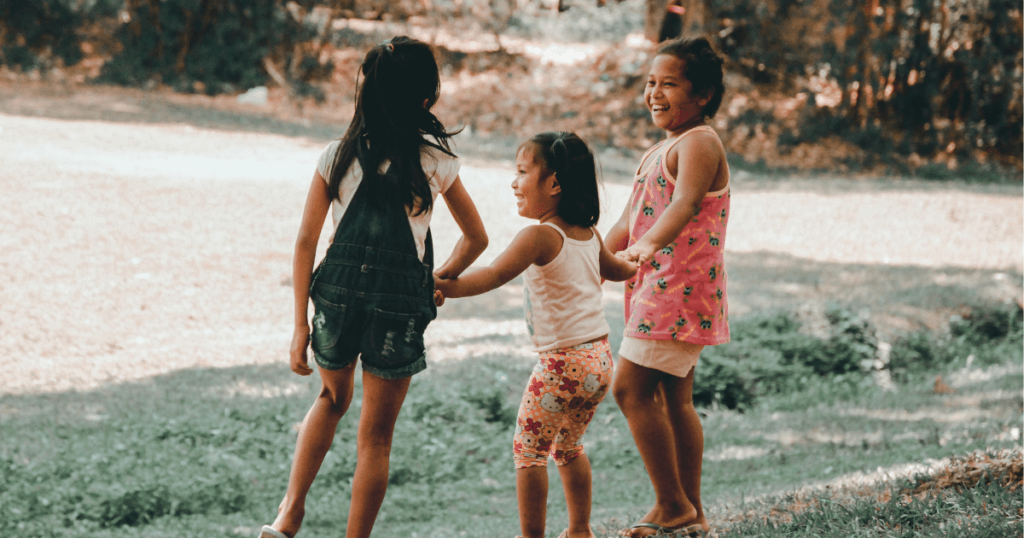 An image of three young girls smiling and playing outside