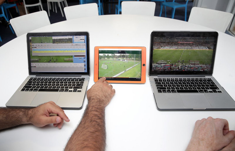 Two men watching soccer footage on laptops and tablet