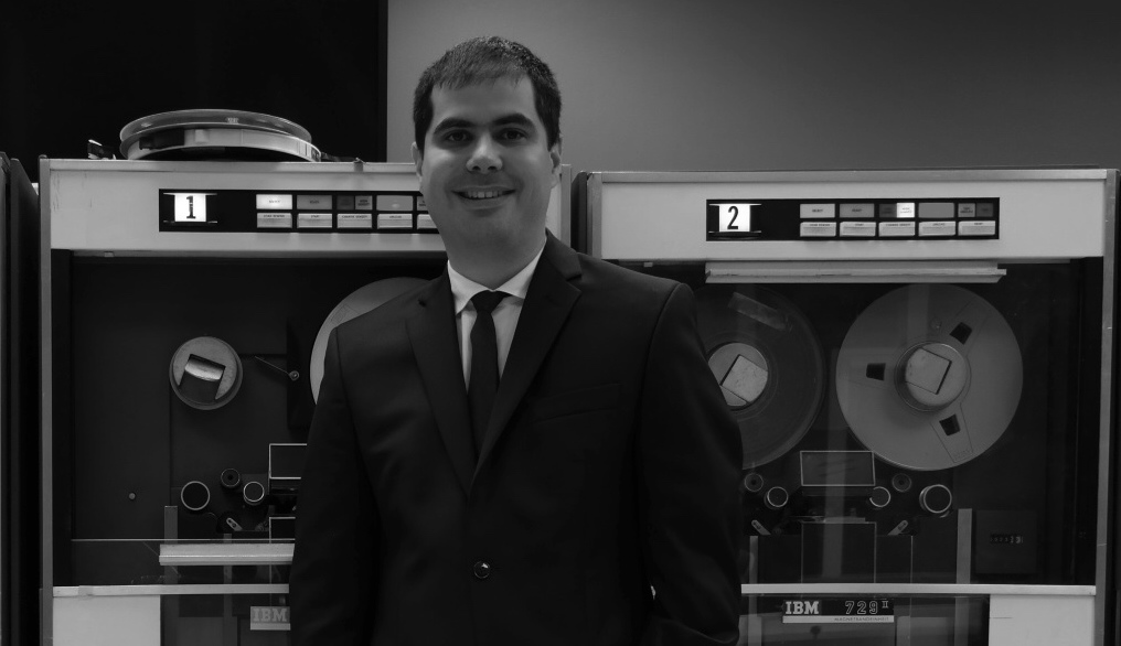 Joël Franusic standing in front of two IBM 729 reel-to-reel tape machines for the IBM 1401