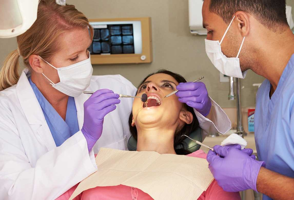 A dentist and dental assistant work on a patient.