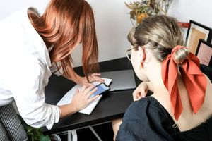 Image of two women looking at a mobile phone on a desk.