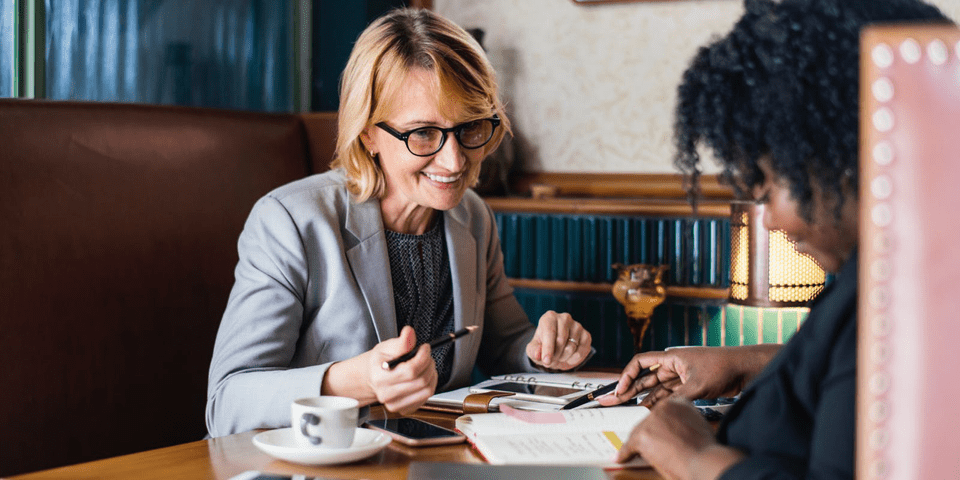 Accountant presents to client with visual graphics as well as number on documents on table with cups of coffee as client looks at Futrli reports #reporting
