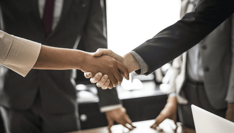 Accountants shake hands across wooden table at networking event and ask questions from business owner
