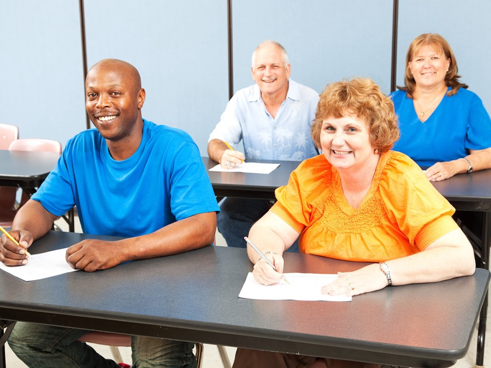 Adult education students sit in classroom during lecture.