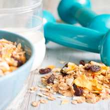 Diet and fitness concept with dumbbells and muesli
