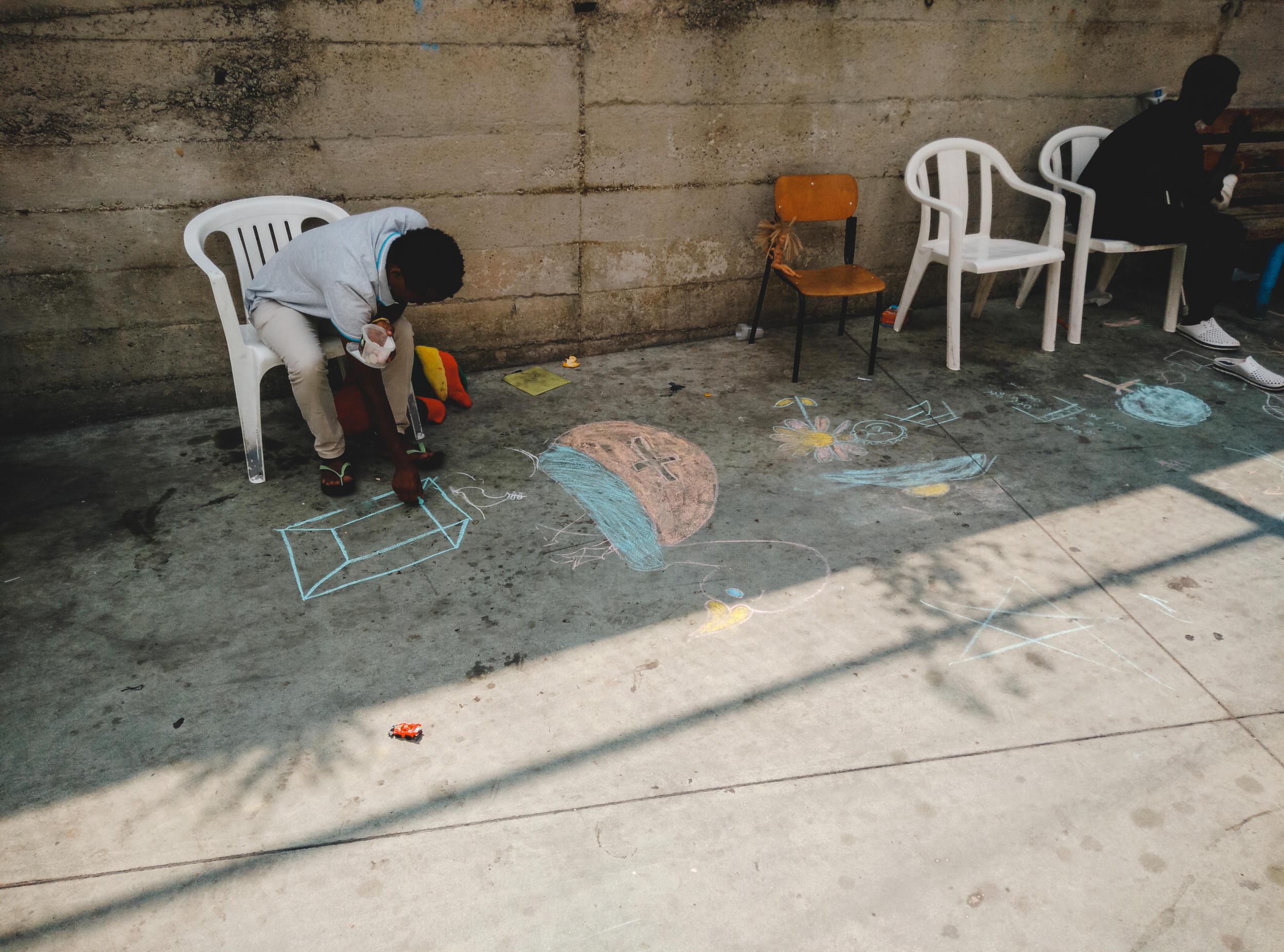 un migrante disegna a terra con un gesso