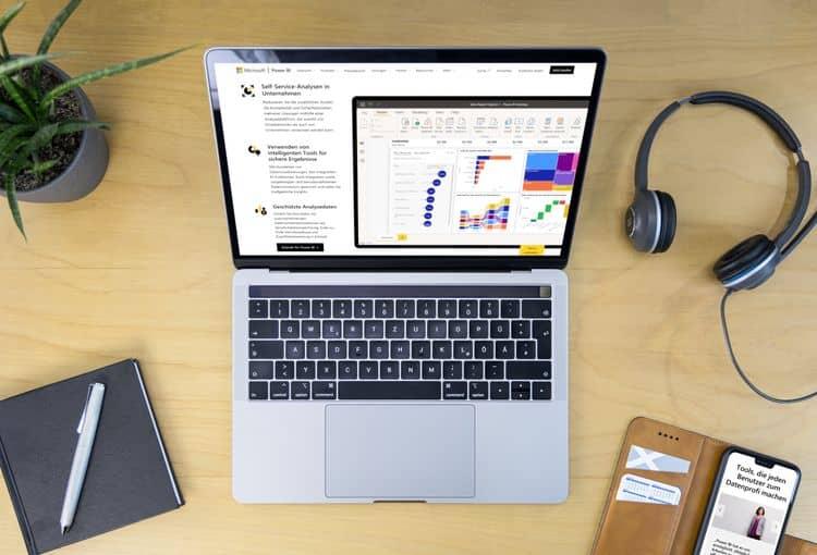 Laptop mit Power BI auf Schreibtisch mit Smartphone, Pflanze, Kopfhörern