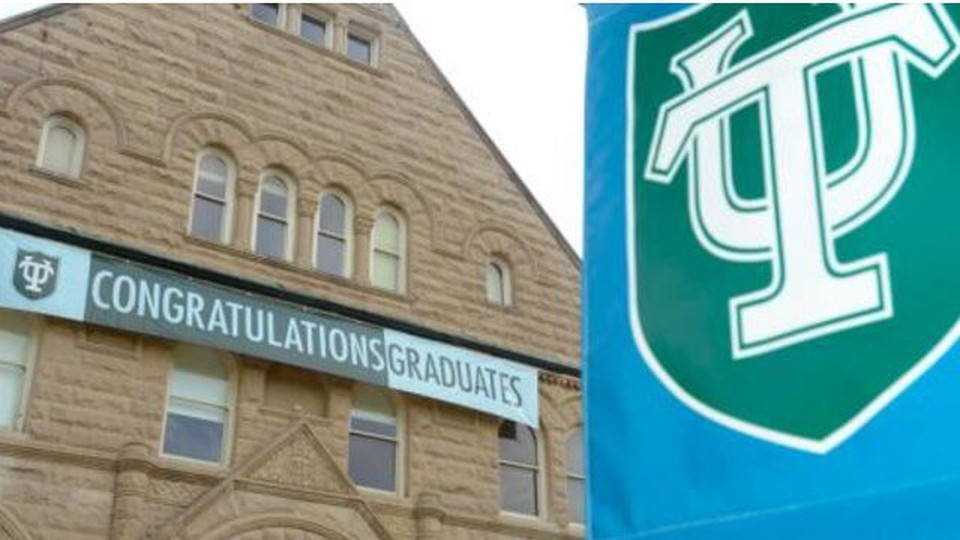 On the left a building with a sign written Congratulations Graduates. On right a Tulane University flag
