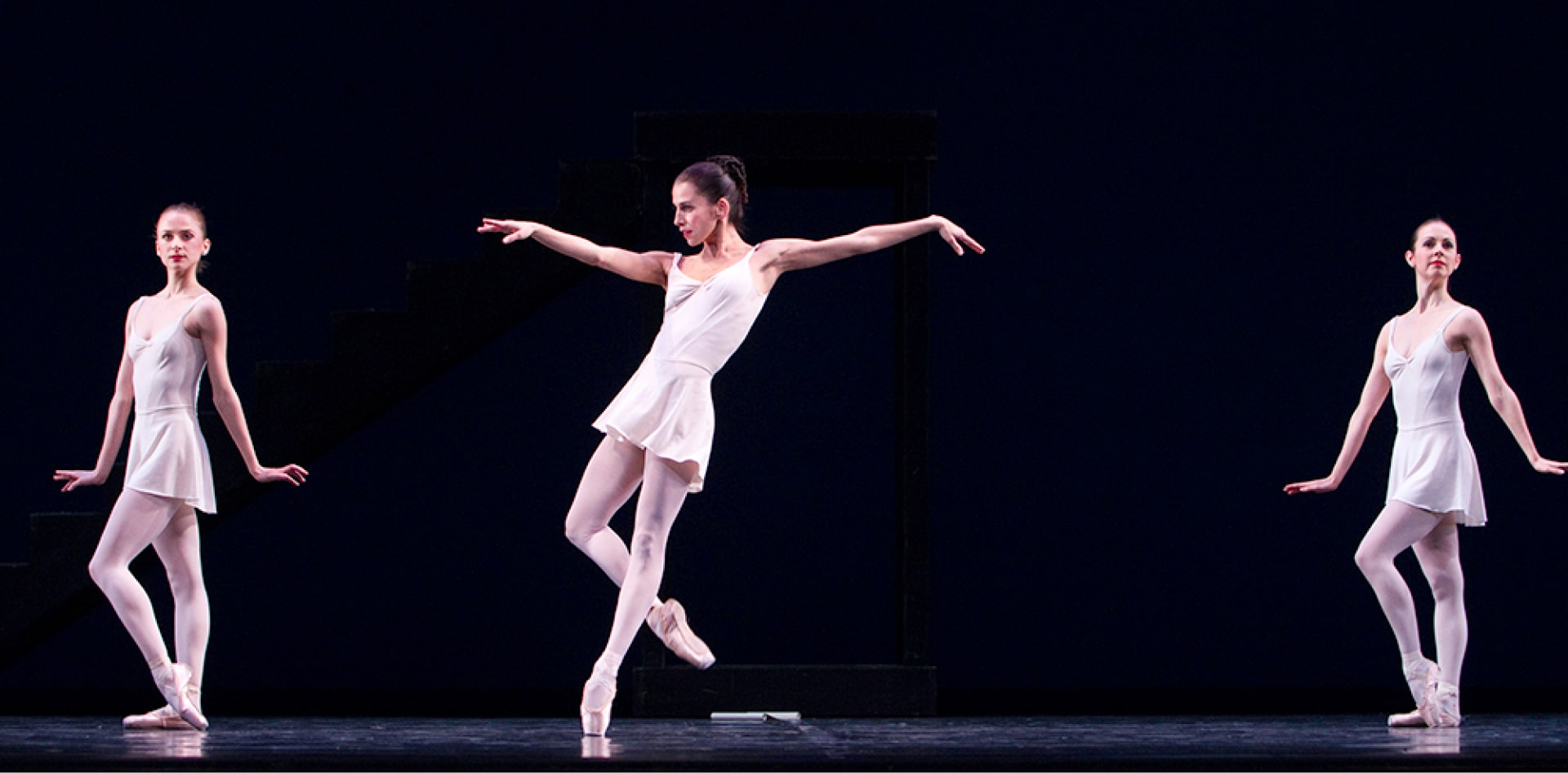 Three ballerinas in short white dresses hold angular poses against dark blue background.