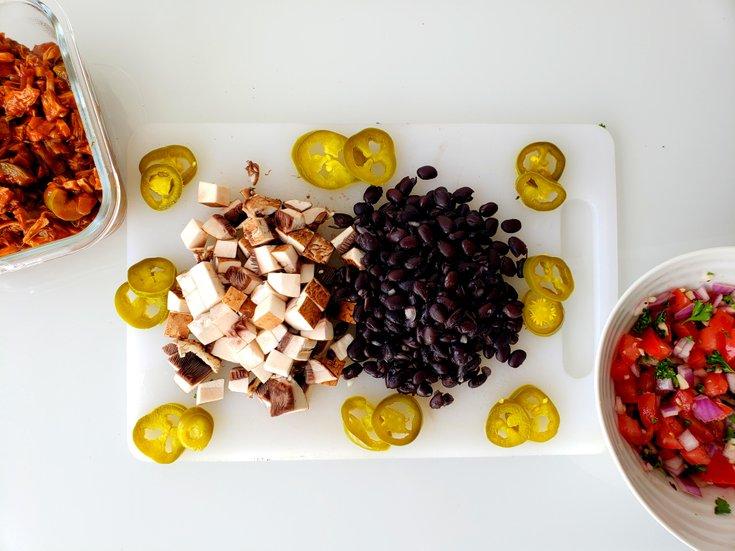 Cutting board with beans, salsa, jackfruit, mushrooms
