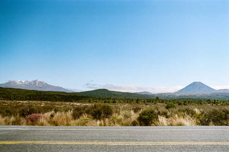 Looking across a road into a scrub desert with two mountains side-by-side in the distance, the left craggy and snow-covered, the right volcanic gray with a cinder cone.