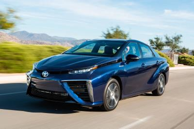 Toyota Mirai hydrogen fuel cell car driving along a road with mountains and scenery in the background