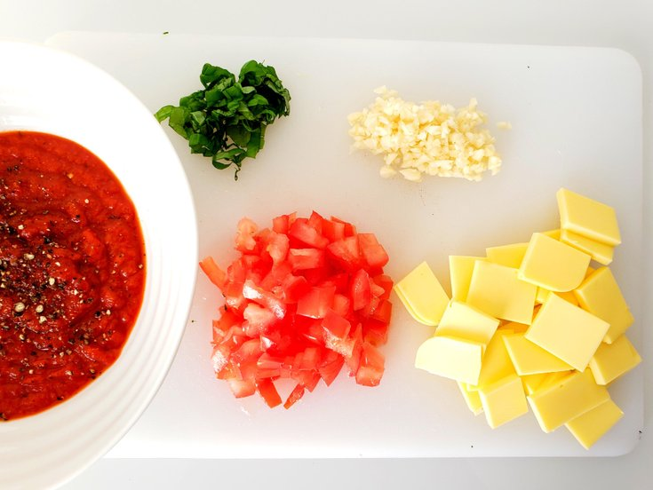 Tomato sauce in bowl, with Cut up Tomatoes, Vegan Mozzarella cheese, Minced Garlic, and Fresh Basil on Cutting Board