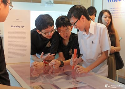 A photo of a tour. Students are looking down into a table showcase.