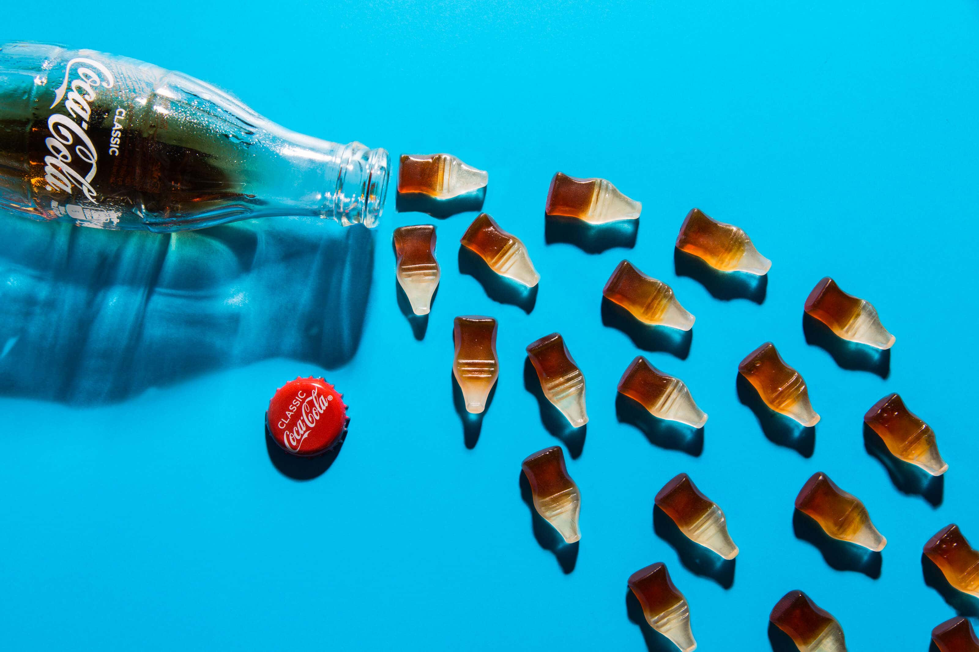 Coca-Cola bottle with coke sweets Pouring out on blue background pop art style