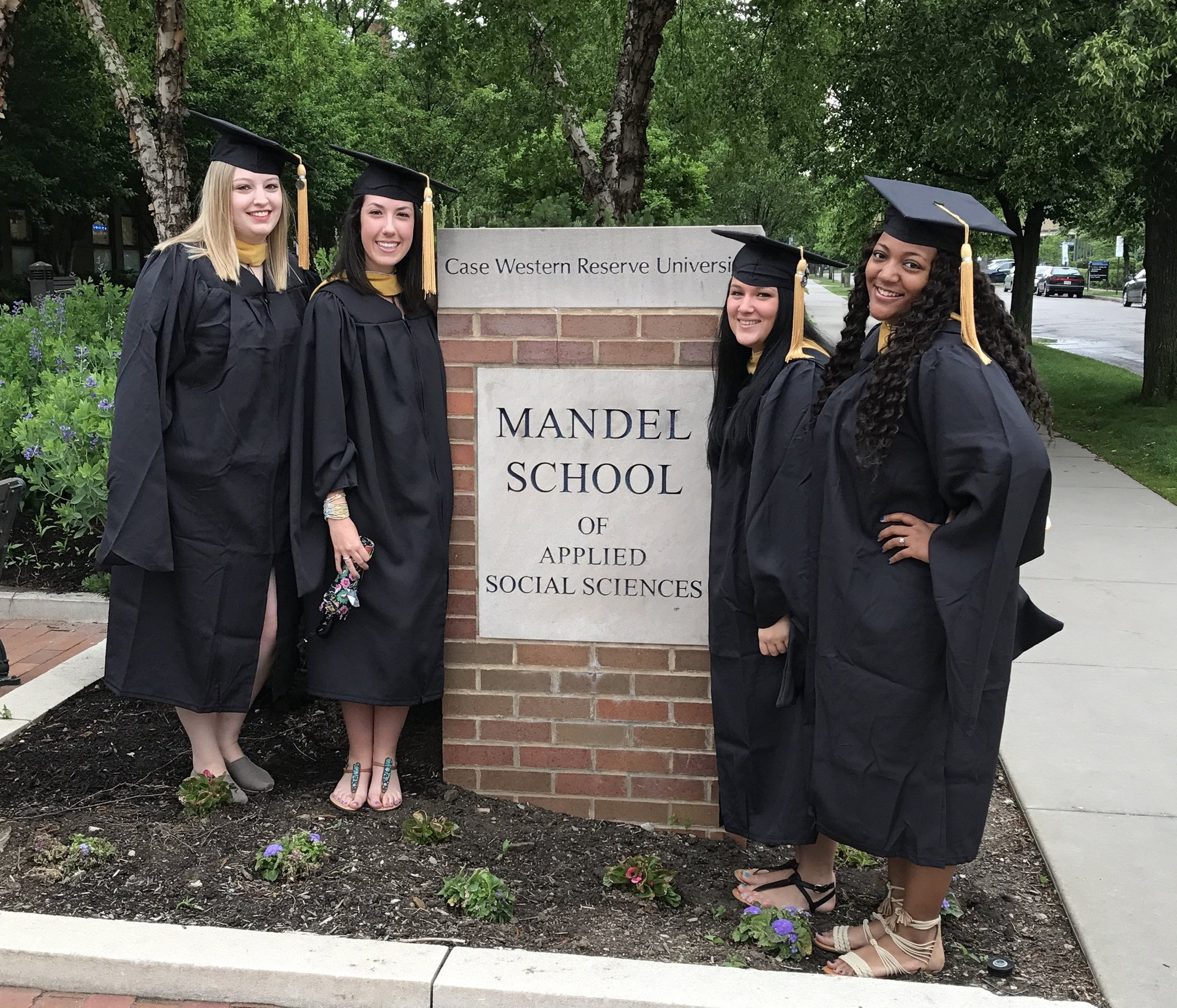 Graduates standing next to Mandel School of Applied Sciences sign
