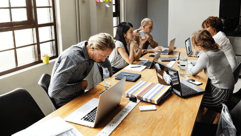 Colleagues working at wooden desk with laptops, notebooks, pens, pencils, paper, notes, documetns, to have meeting and discuss business between staff business owner accountant and use 7 seven best tools #productivity