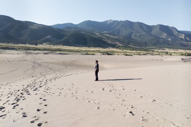 A woman dressed in black pants and a gray shirt looks back toward the camera from a low, sandy hill. In the distance the sand field gives way to desert scrubland, and then eventually to juniper-covered mountains.