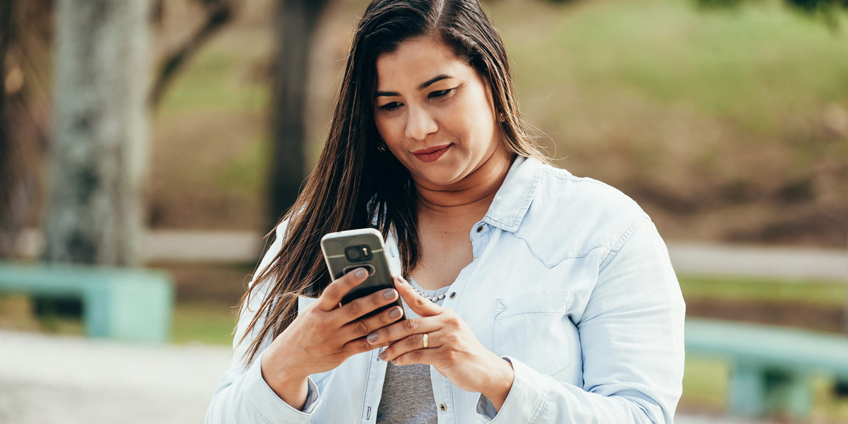 A user standing in a park, working on her phone.