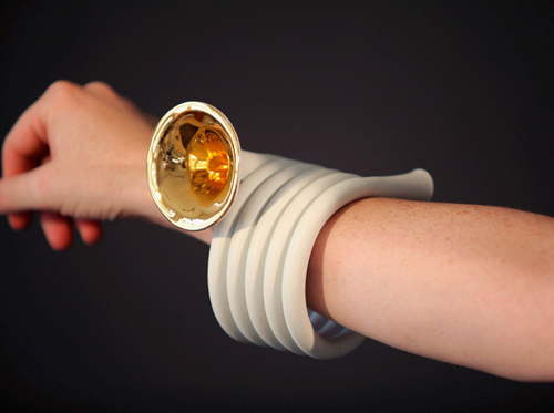 """A """"horn bracelet""""—porcelain tubing wraps around a woman's wrist, like a coil, five rows deep. At the end of the coil is a small brass horn, like a tiny tuba."""