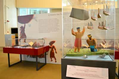 There is a small showcase with paper sculptures, sitting on top of an audio kiosk. It is of a man by the riverside holding a boulder and several ships aloft in the air, while a Sultan bows before him.