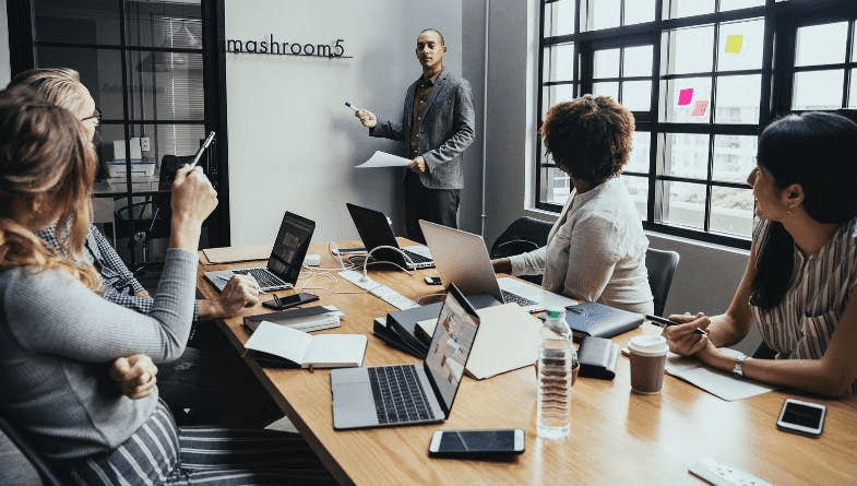Advisor stands at board and presents business reports to employees and business owners at desk with laptops, notebooks, pens, documents #reporting