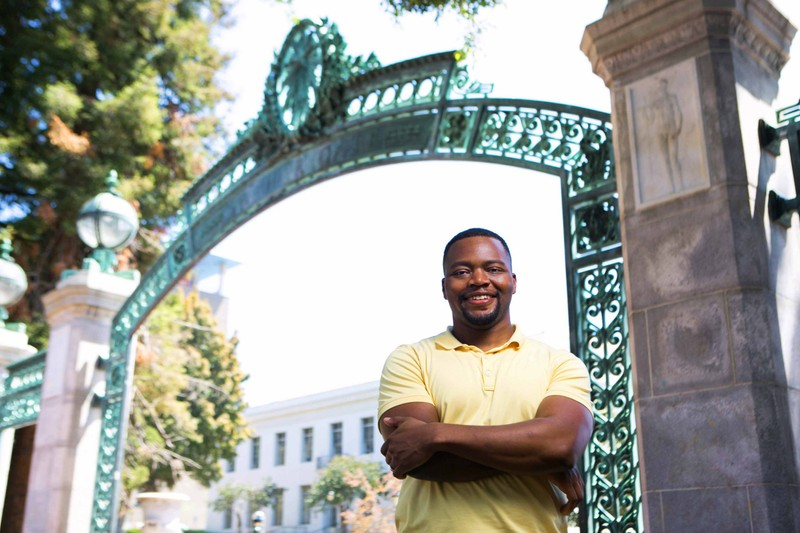 A smiling student in a yellow shirt stands in front of Sather Gate at the UC Berkeley