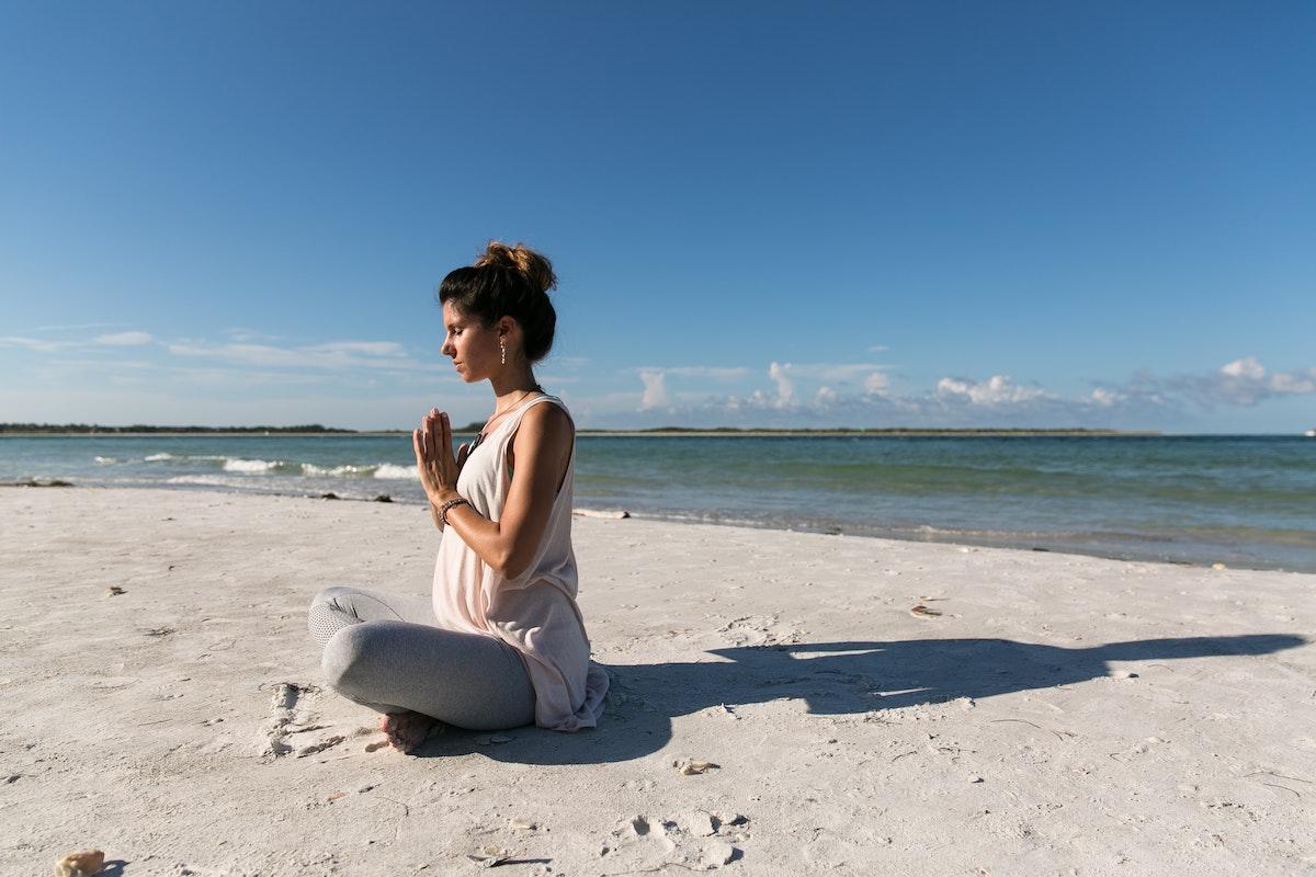 embarazada haciendo yoga en la playa