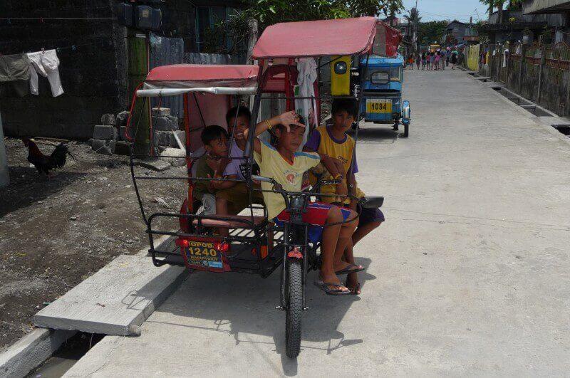 Op de terugweg lopen we langs een tricycle met een paar jongens erop