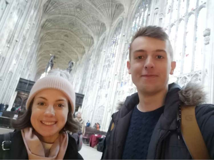 Myself and Naomi, smiling in the foreground, with the inside of a cathederal in Cambridge in the background.