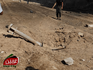 """Photo shows the remains of one of the Volcano rockets used in the chemical attack in East Ghouta on 21 August 2013. The rocket, whose warhead is bent face down in the ground, is lying in rubble near a road. There is a man and two people further in the background walking on the road. The photo includes a logo in the bottom left corner that reads """"Erbin"""" in Arabic and """"Erbin city"""" in English. The photo appeared in a Brown Moses article in 2013."""
