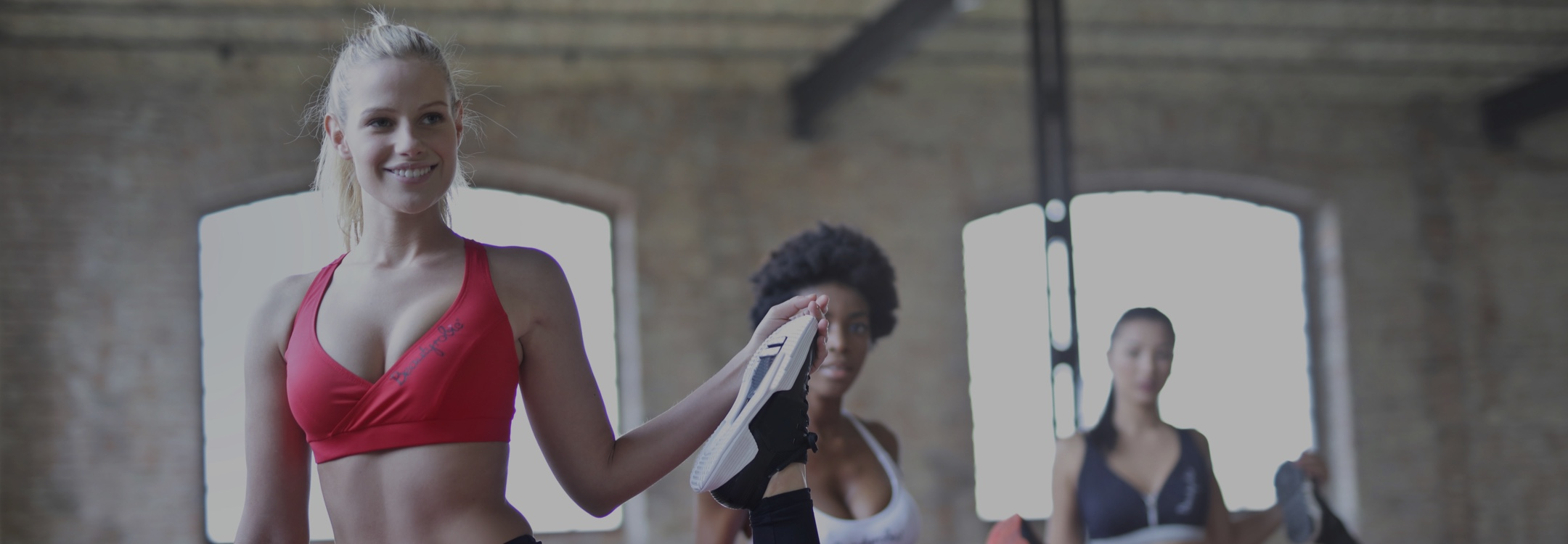 Image of three women in the gym, stretching before a group workout