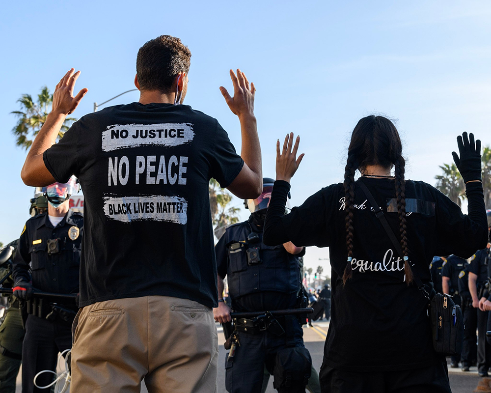 Two protestors in front of a police line with their hands up.